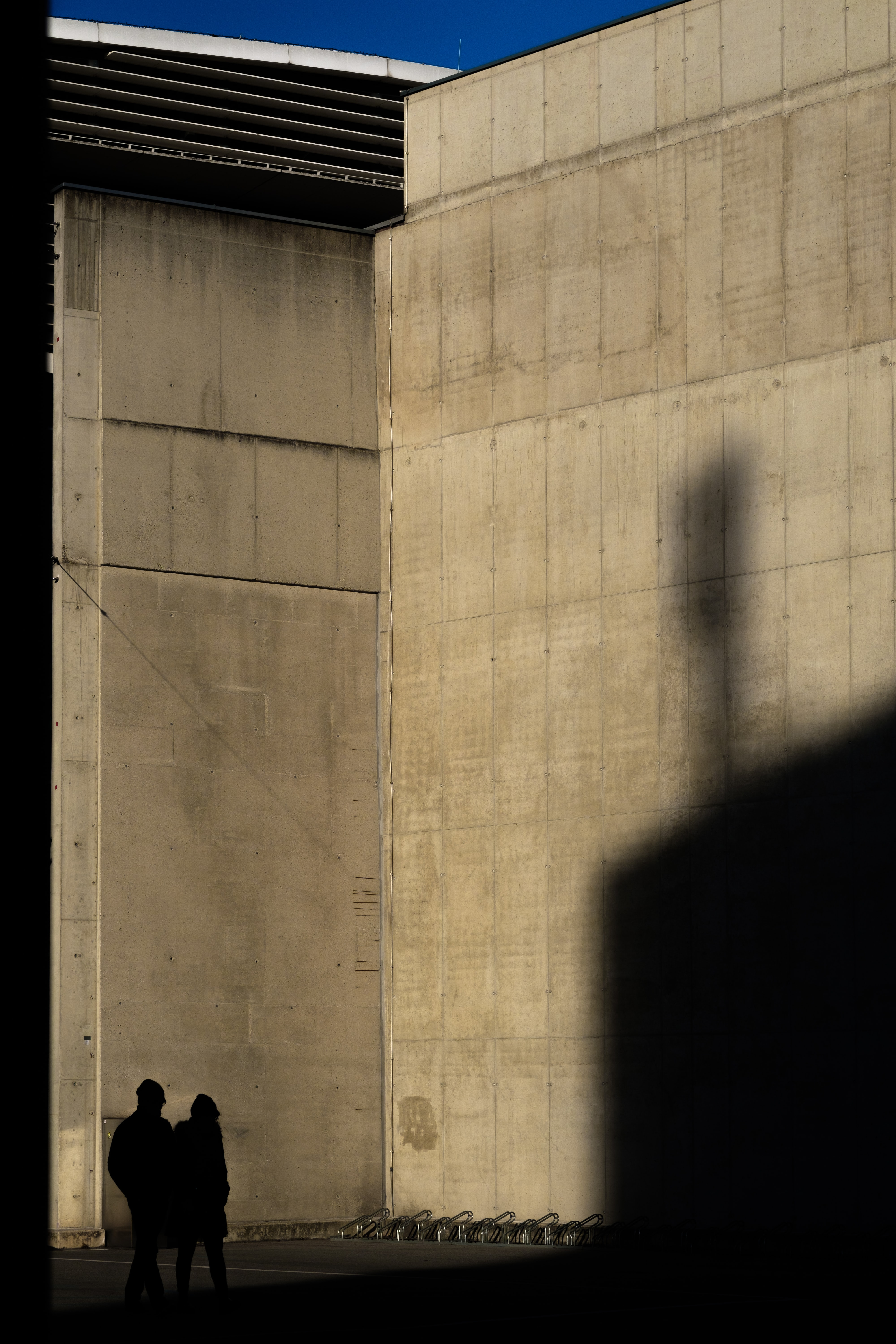 two silhouette of person standing near wall