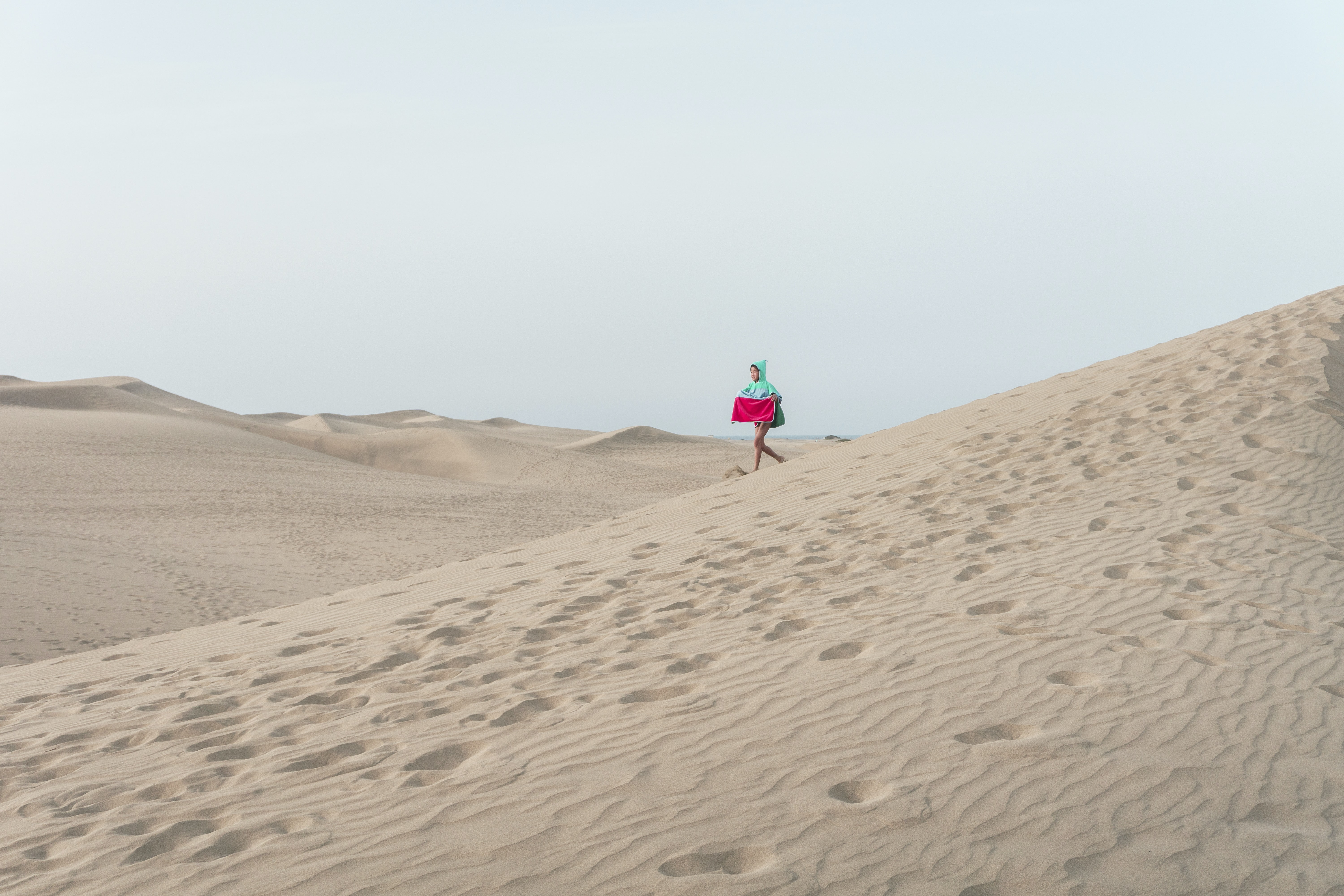 photo of person walking on desert holding red box
