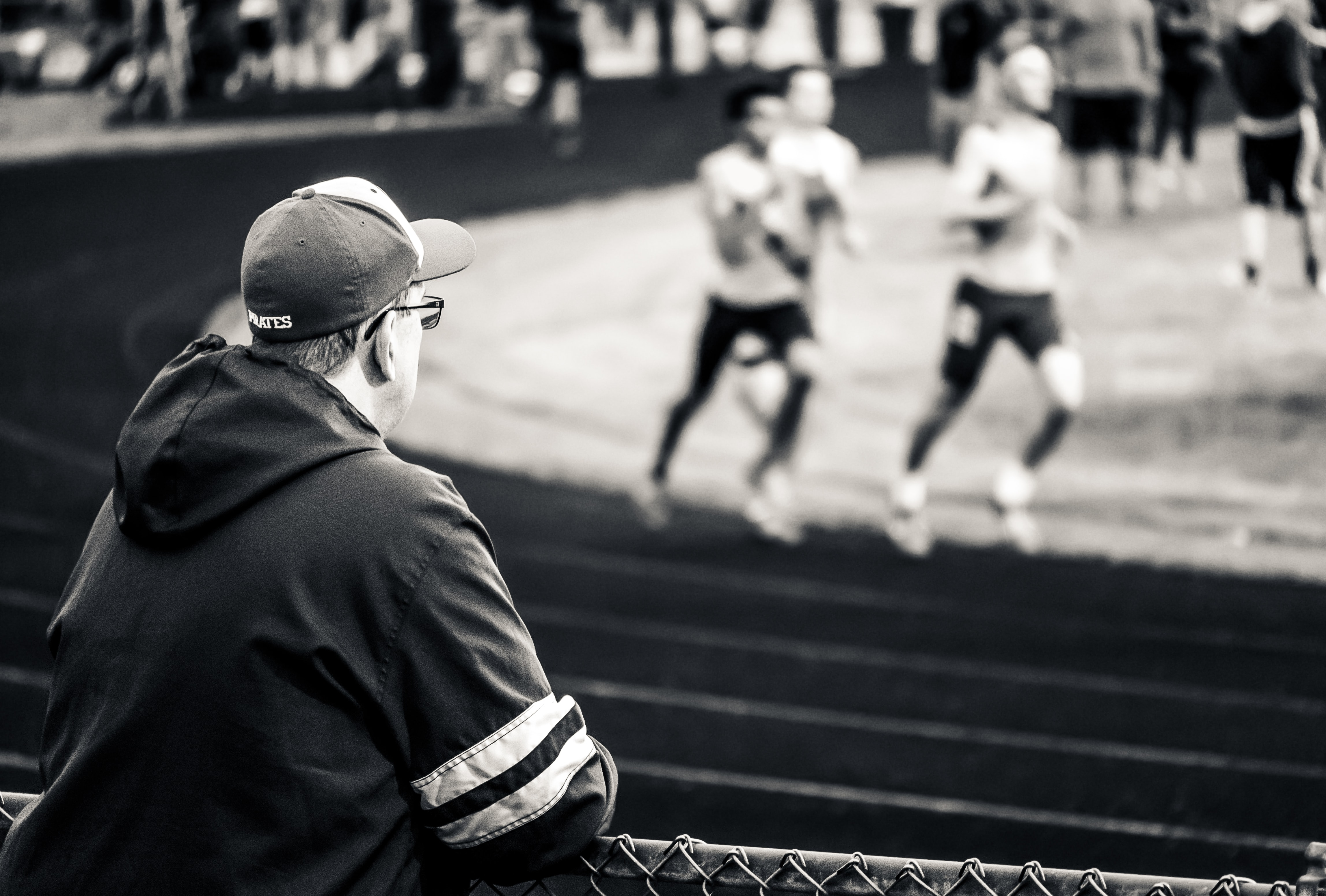 man wearing hoodie watching three people running on field