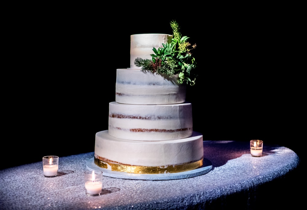4-tier cake on top of gray table with three votive candles