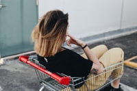 woman sitting on shopping cart near the wall
