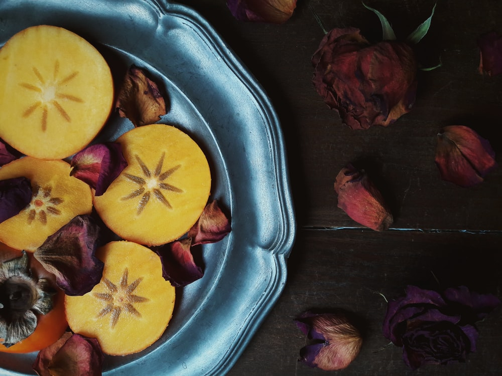 sliced persimmon fruits and withered red roses on gray plate
