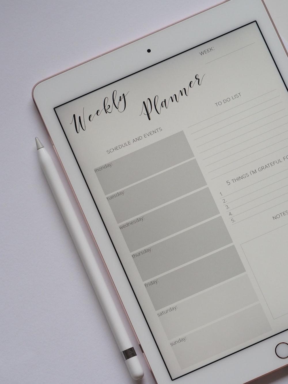 Fotografía laica plana del iPad plateado encendido junto al Apple Pencil