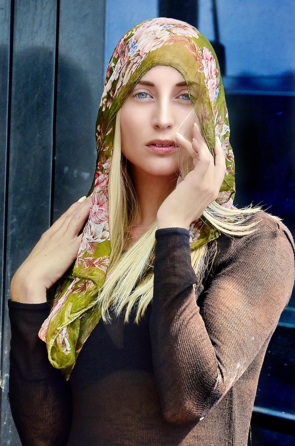 woman wearing headdress touching her cheek