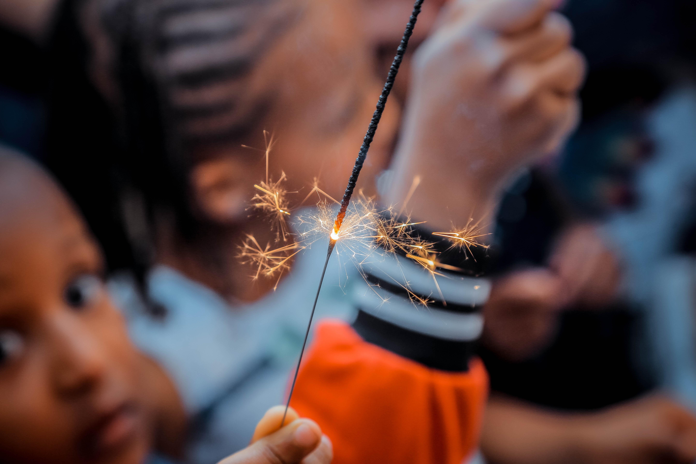 person holding sparkler beside boy