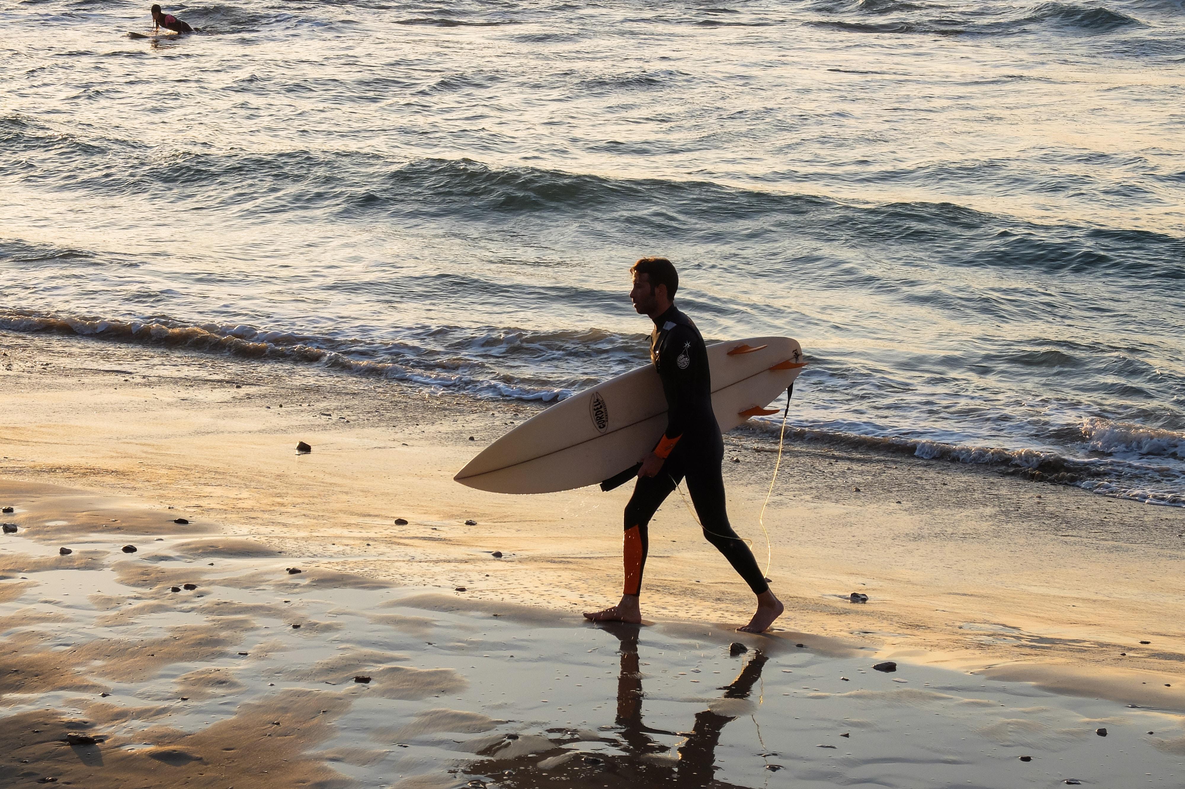 man carrying surfboard while walking on seashore at daytime