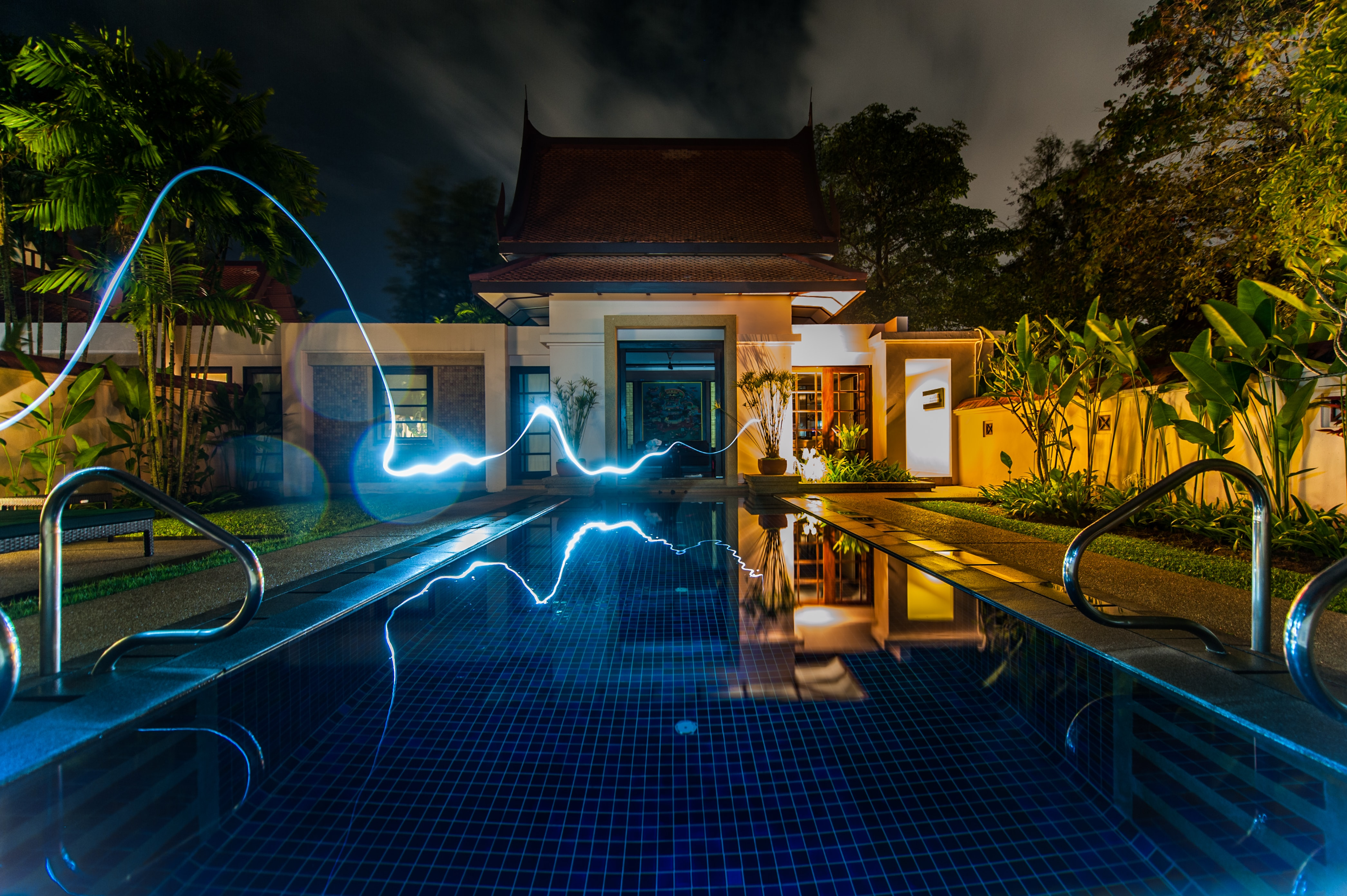 reflection of blue light crossing above pool near house during nighttime
