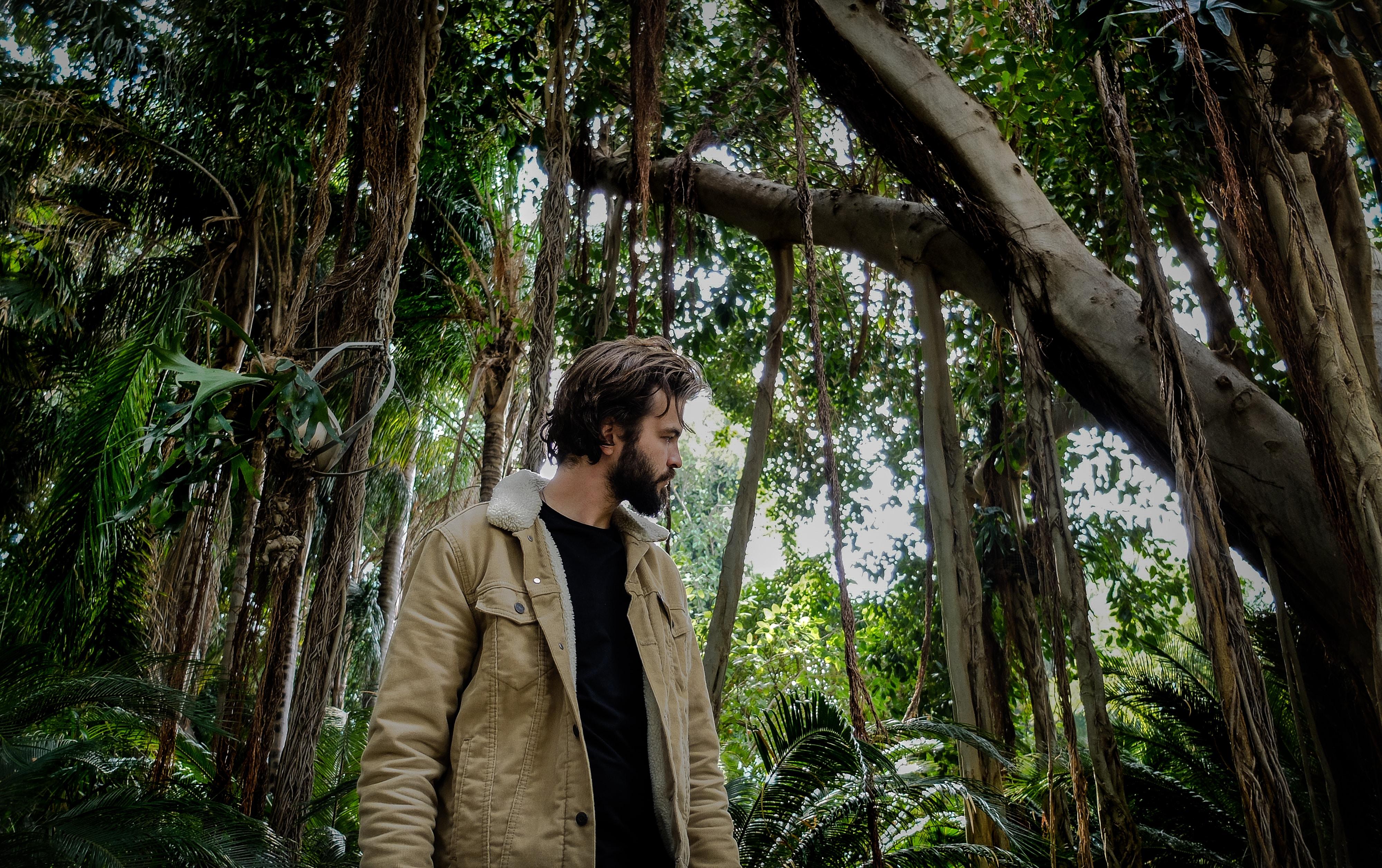 man walking under tree