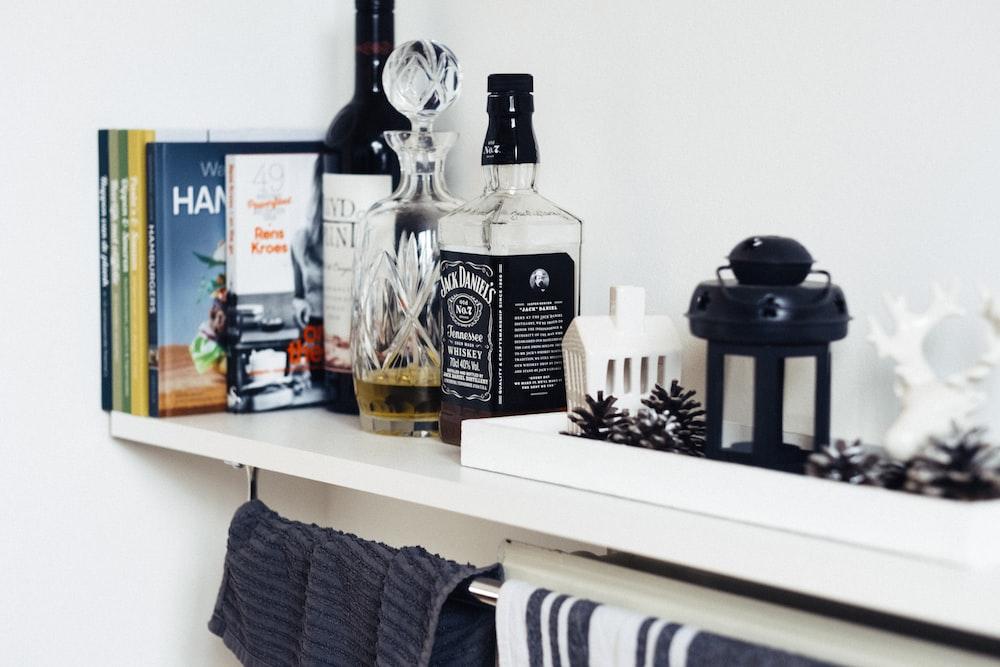 books beside decanter beside Jack Daniel's whisky bottle on wooden shelf
