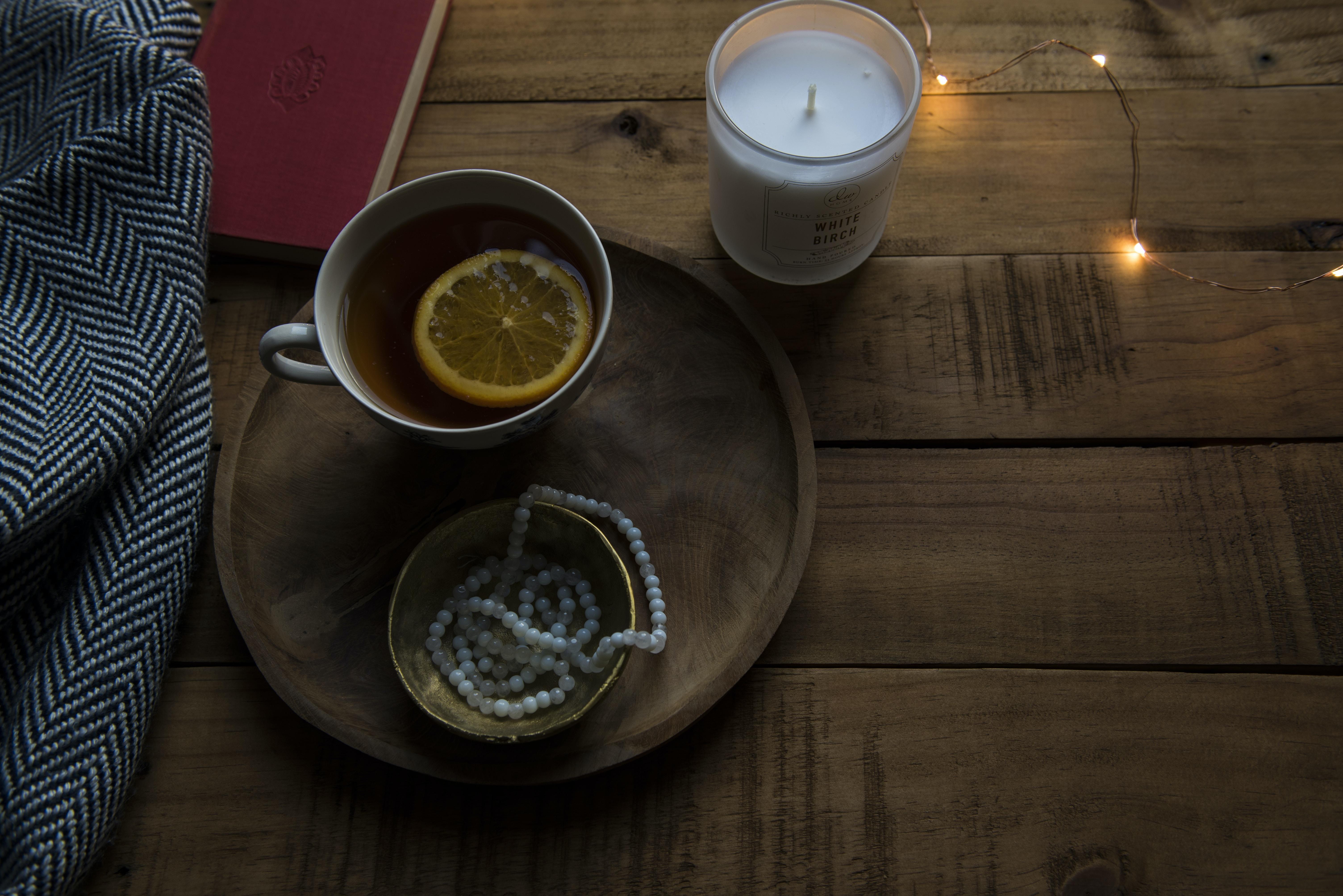ceramic mug on wood tray near candle