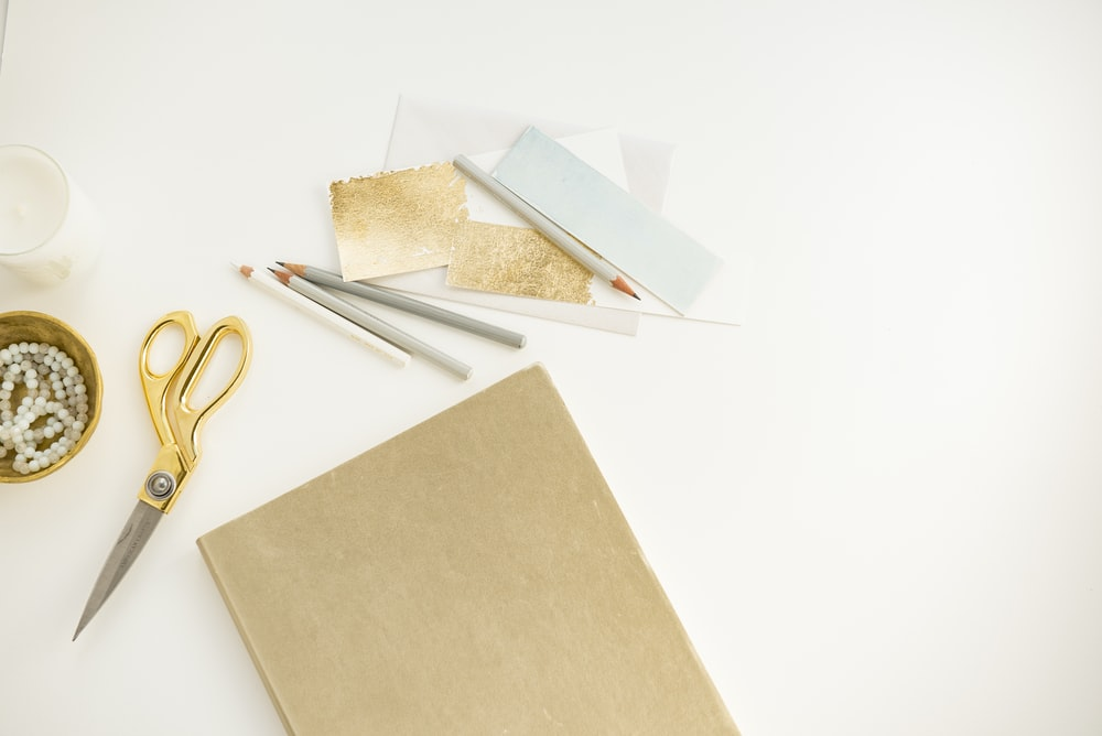 yellow handled scissors beside brown paper