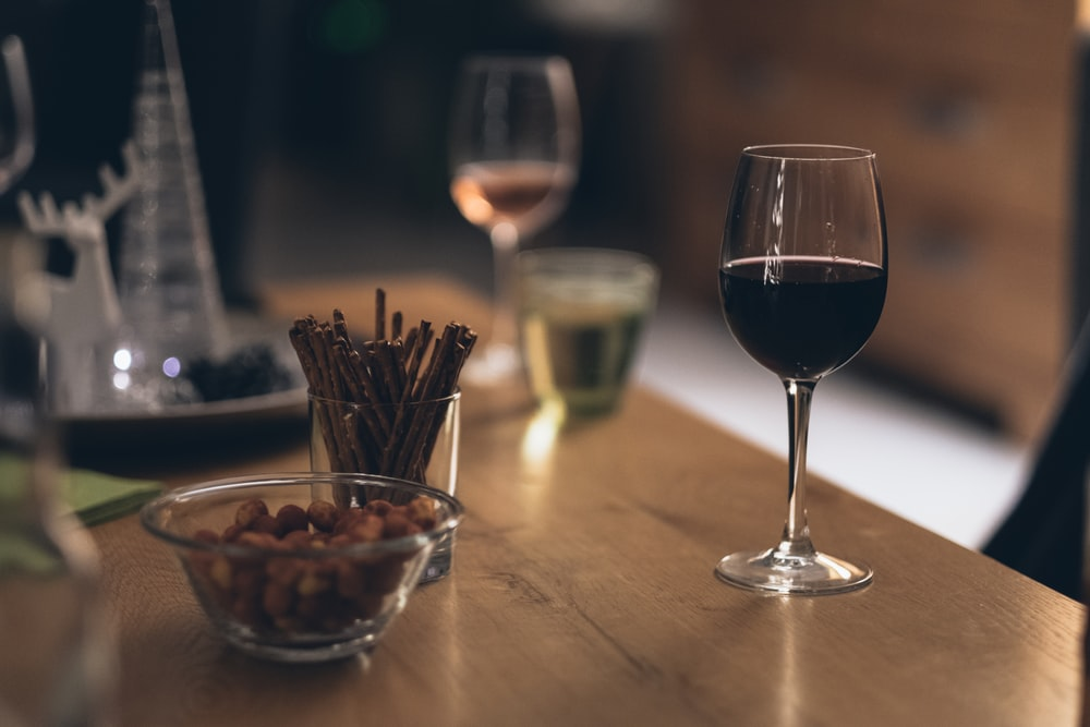 black liquid in clear wine glass on brown wooden table