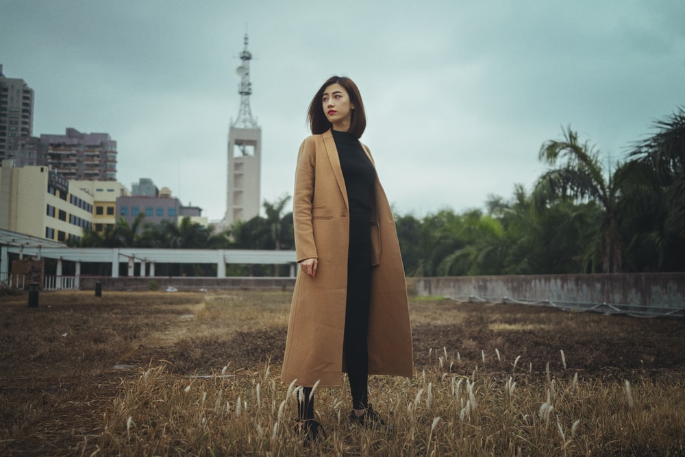 woman wearing brown coat standing on brown grass