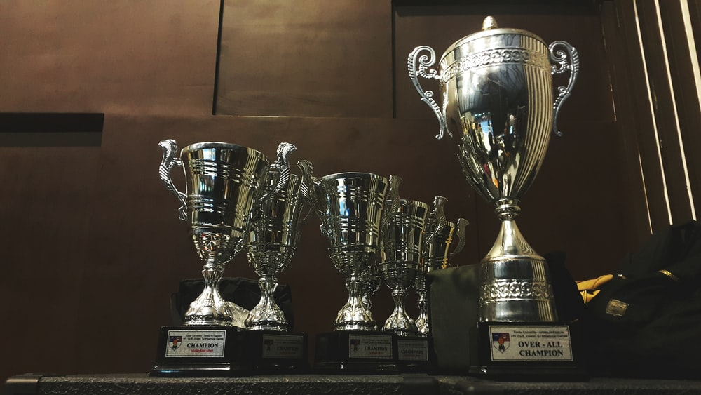several silver and gold trophies on wooden surface