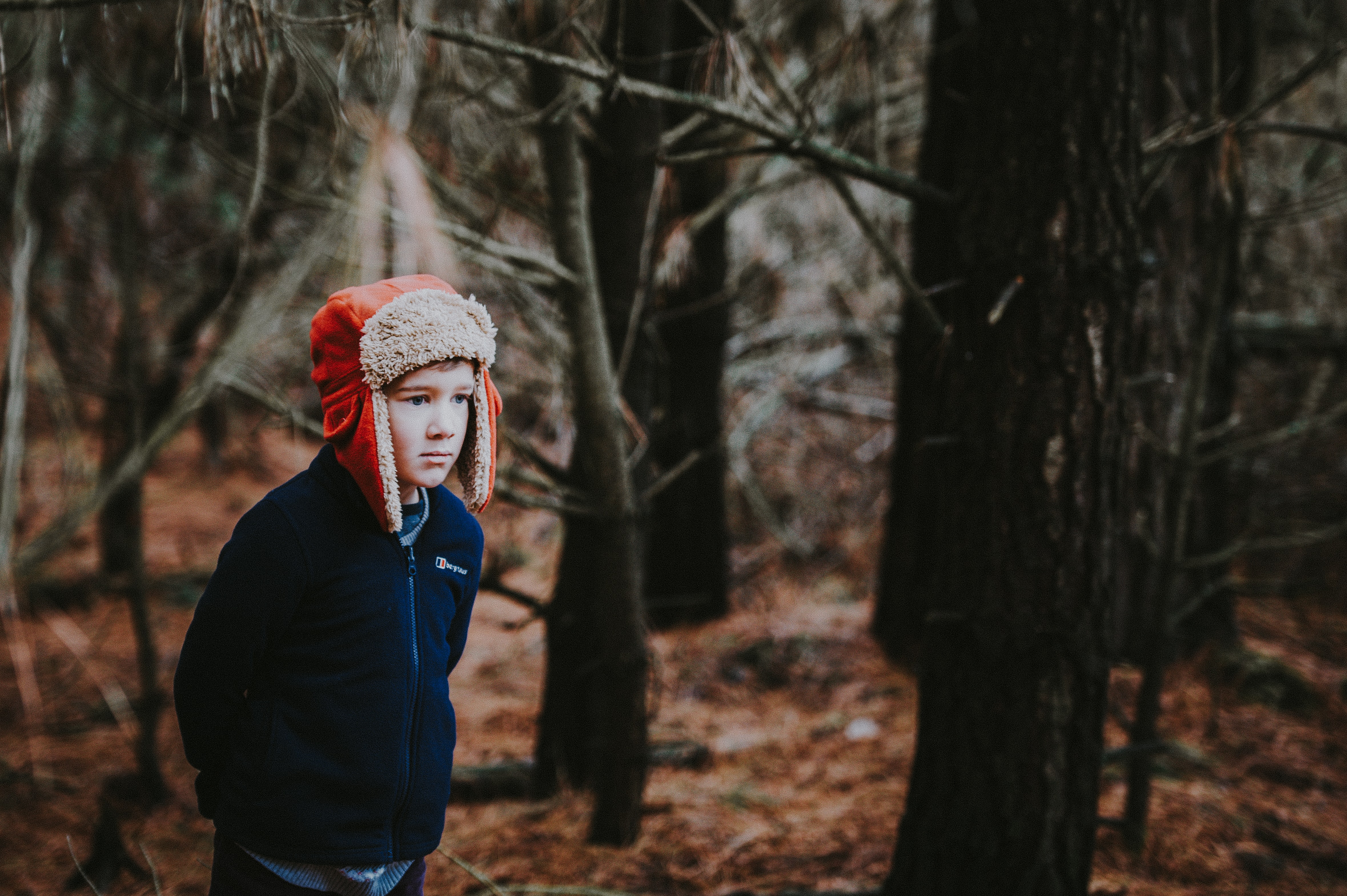 boy wearing aviator hat surrounded by trees