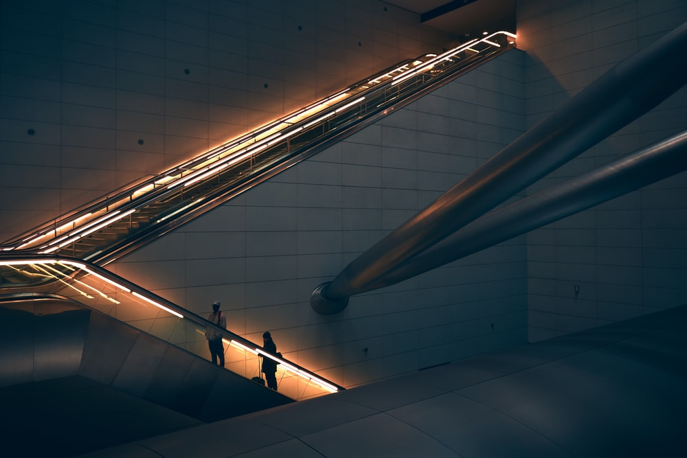two person standing on escalator