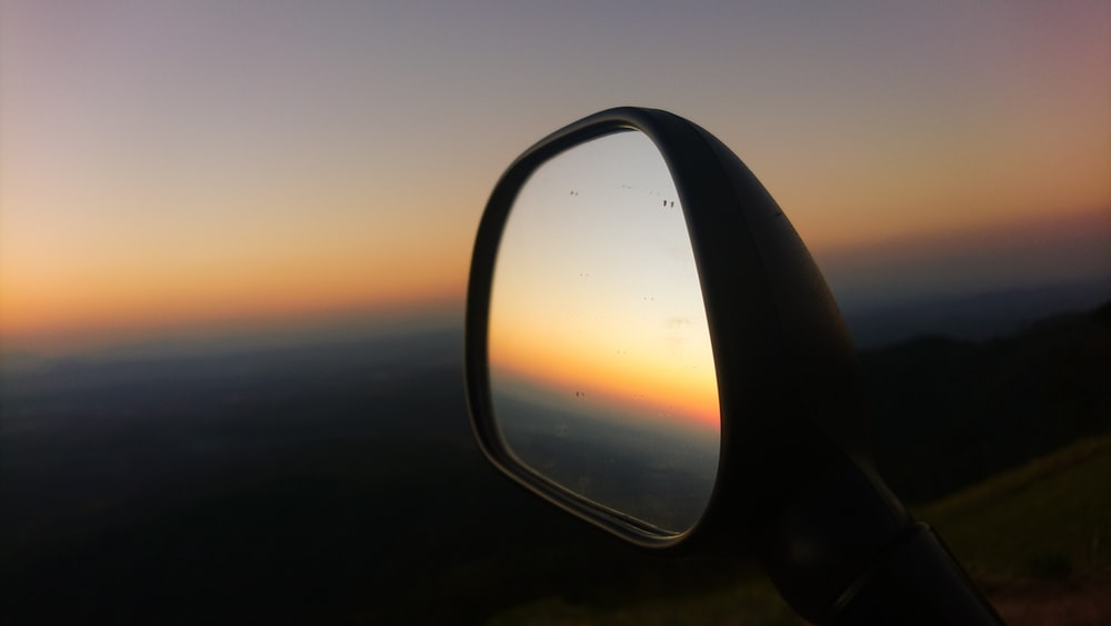 selective focus photo of vehicle side mirror during golden hour