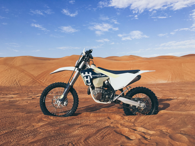 black and white dirt bike on sand