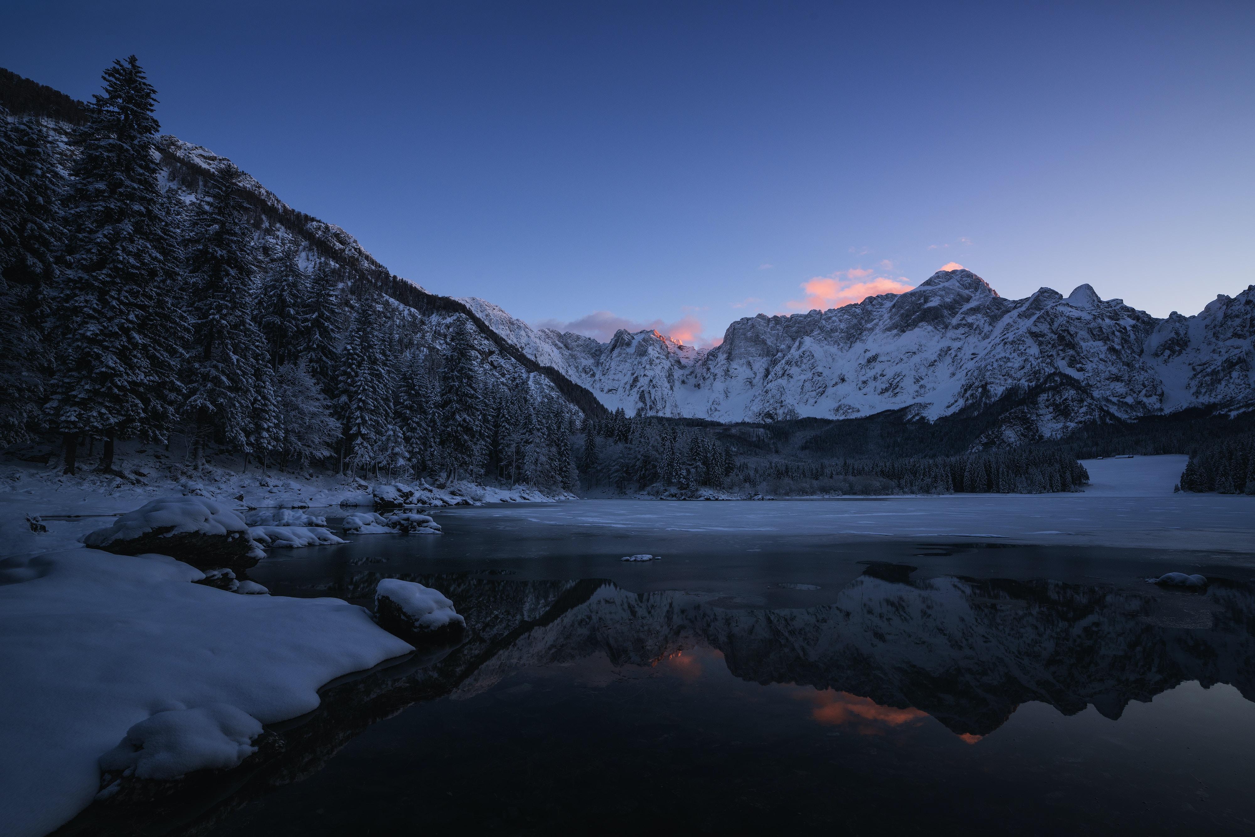 body of water near mountain at dawn