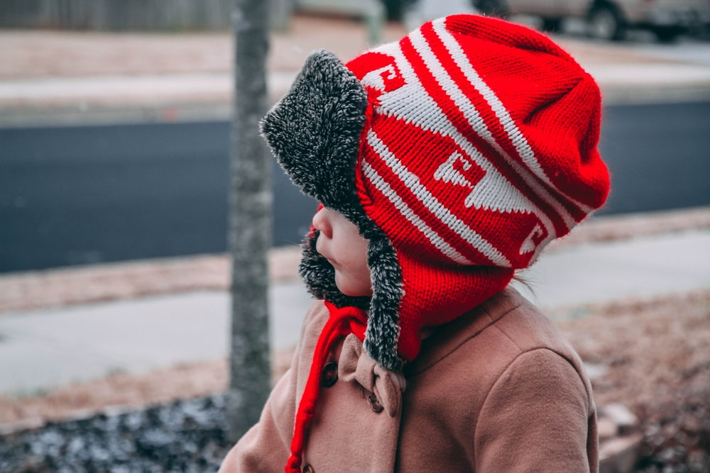 toddler wearing red and white knit hat near road during daytime
