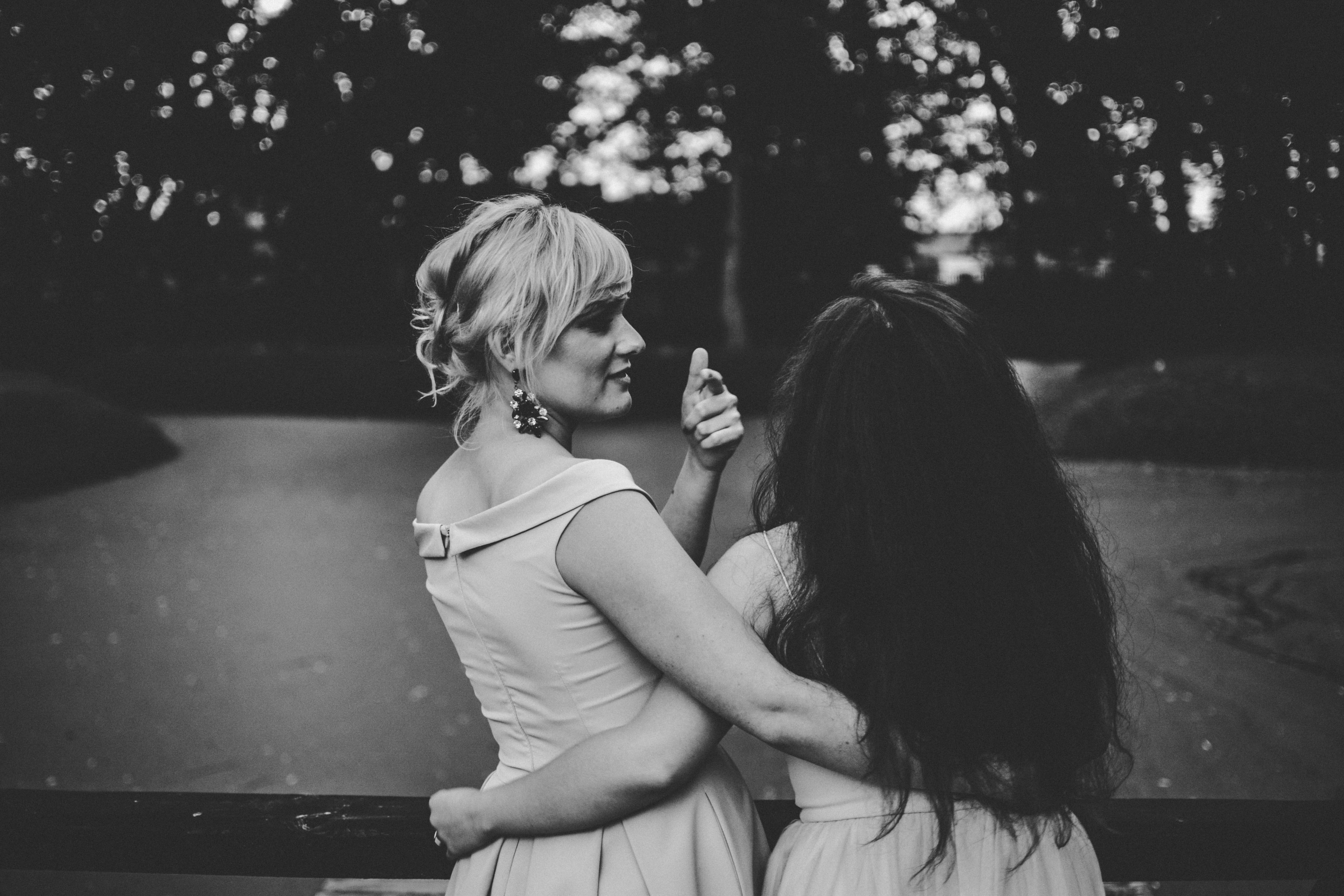 grayscale photography of two women holding each others waist