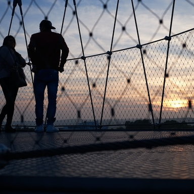 man and woman standing on hanging bridge