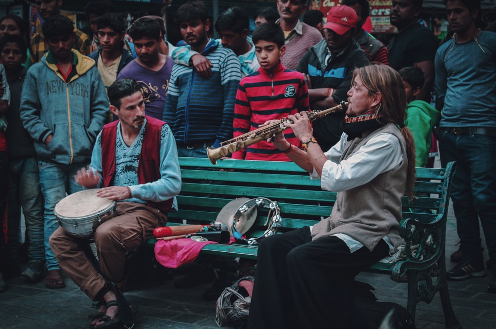 people gathering looking at the man sitting on bench playing wind instrument