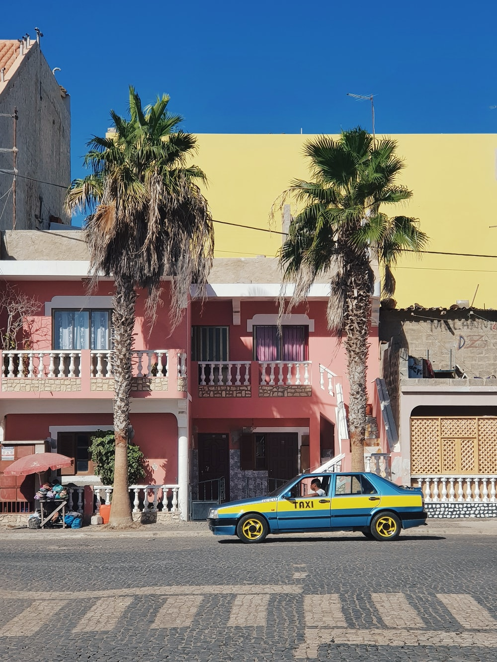 blue and yellow taxi parked near palm tree