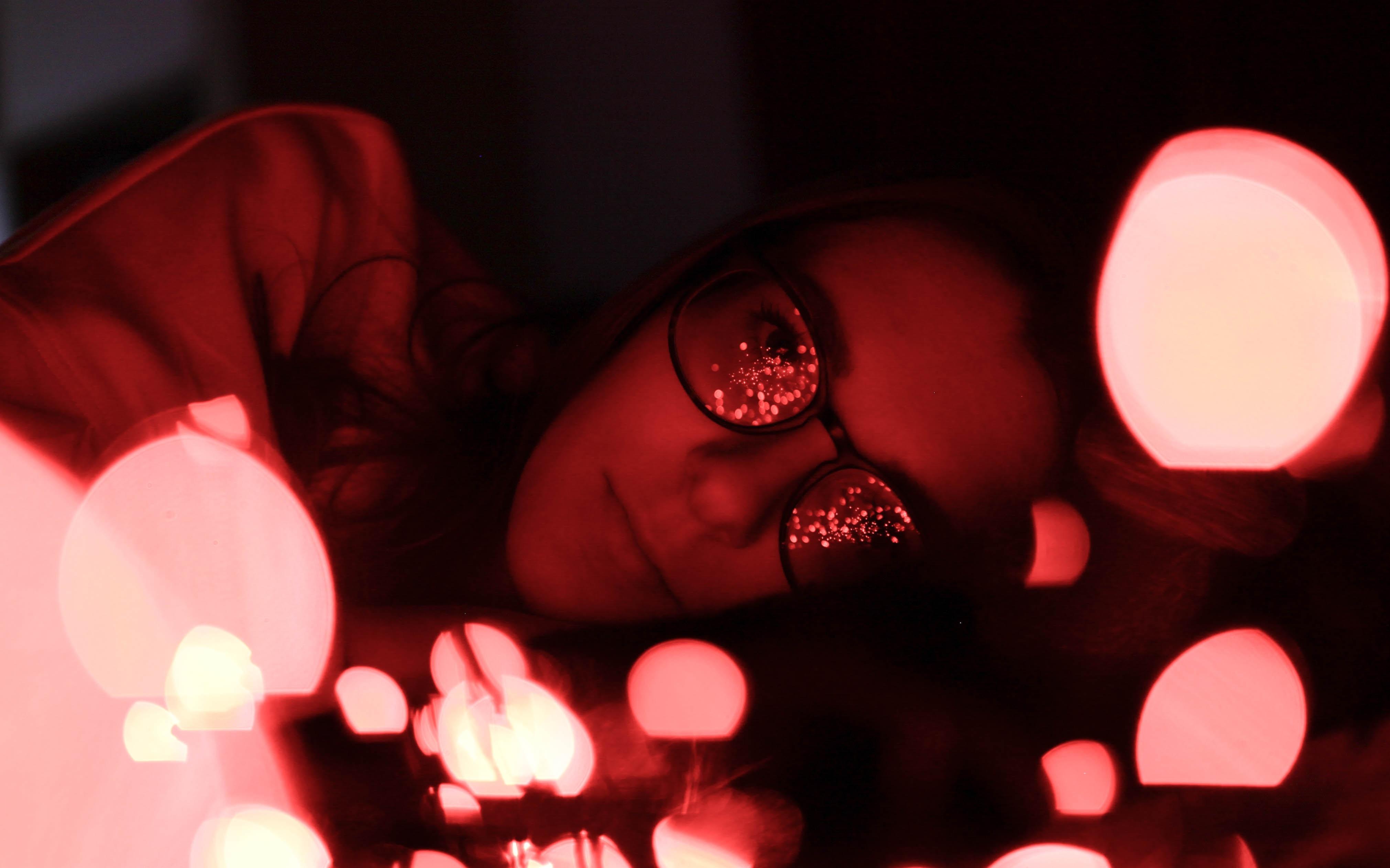 bokeh photography of woman wearing eyeglasses while lying