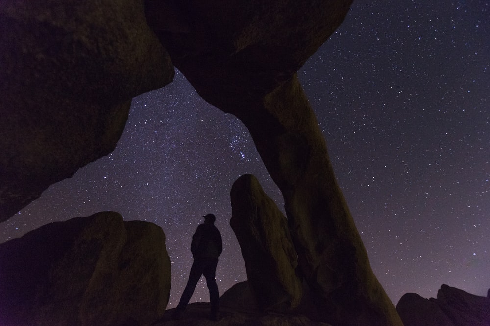 silhouette of person under rock formation at night time