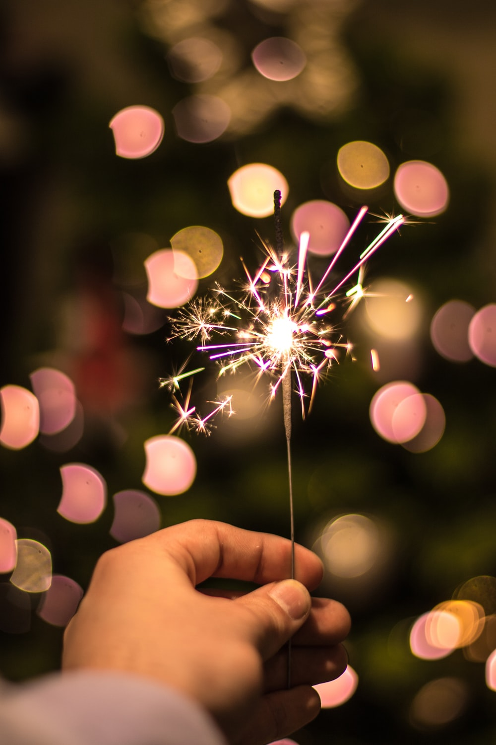 bokeh photography of person holding fireworks