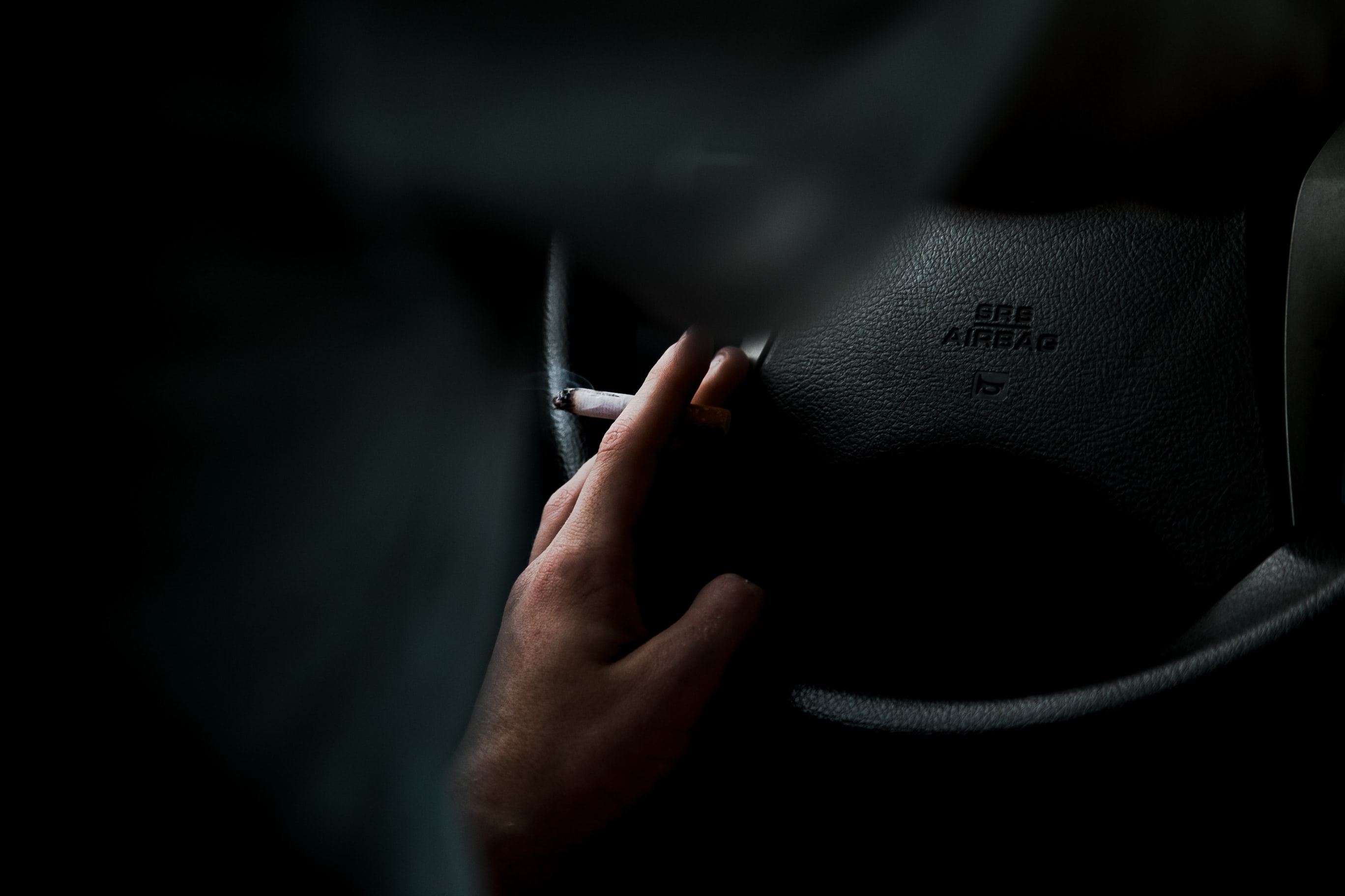closeup photo of person's left hand on top of vehicle steering wheel while holding lighted cigarette
