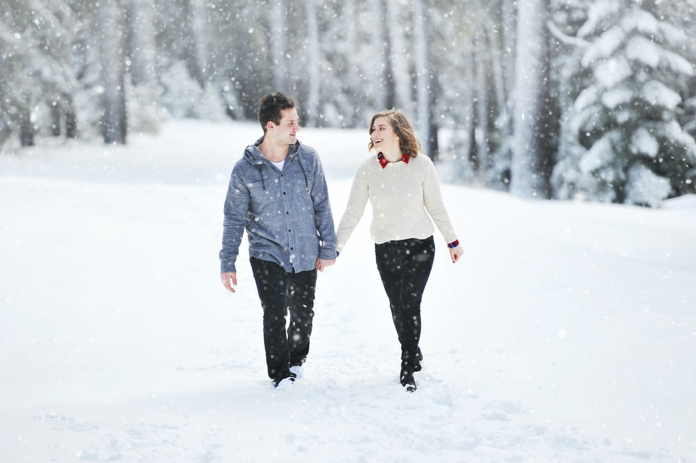 couple walking on snow near trees during daytime