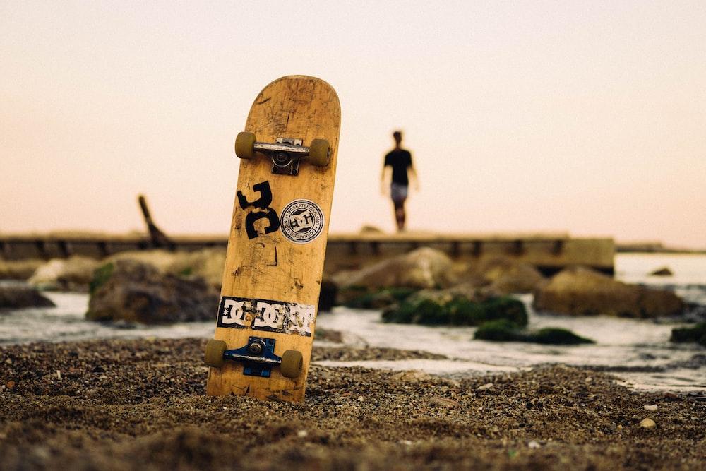 selective focus photography of brown skateboard near shoreline