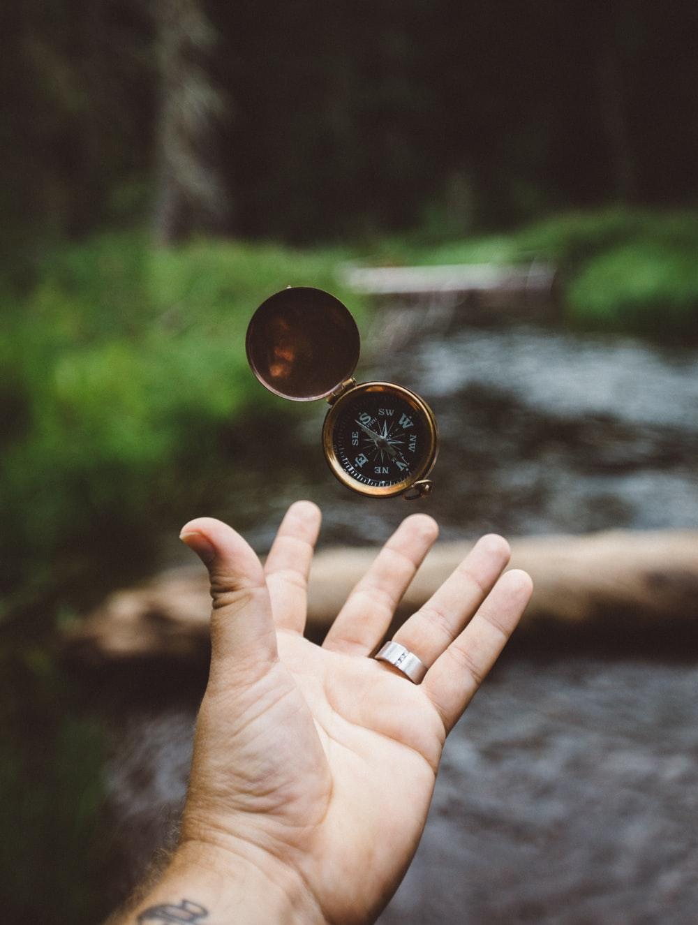 tilt-shift photography of person catching compass