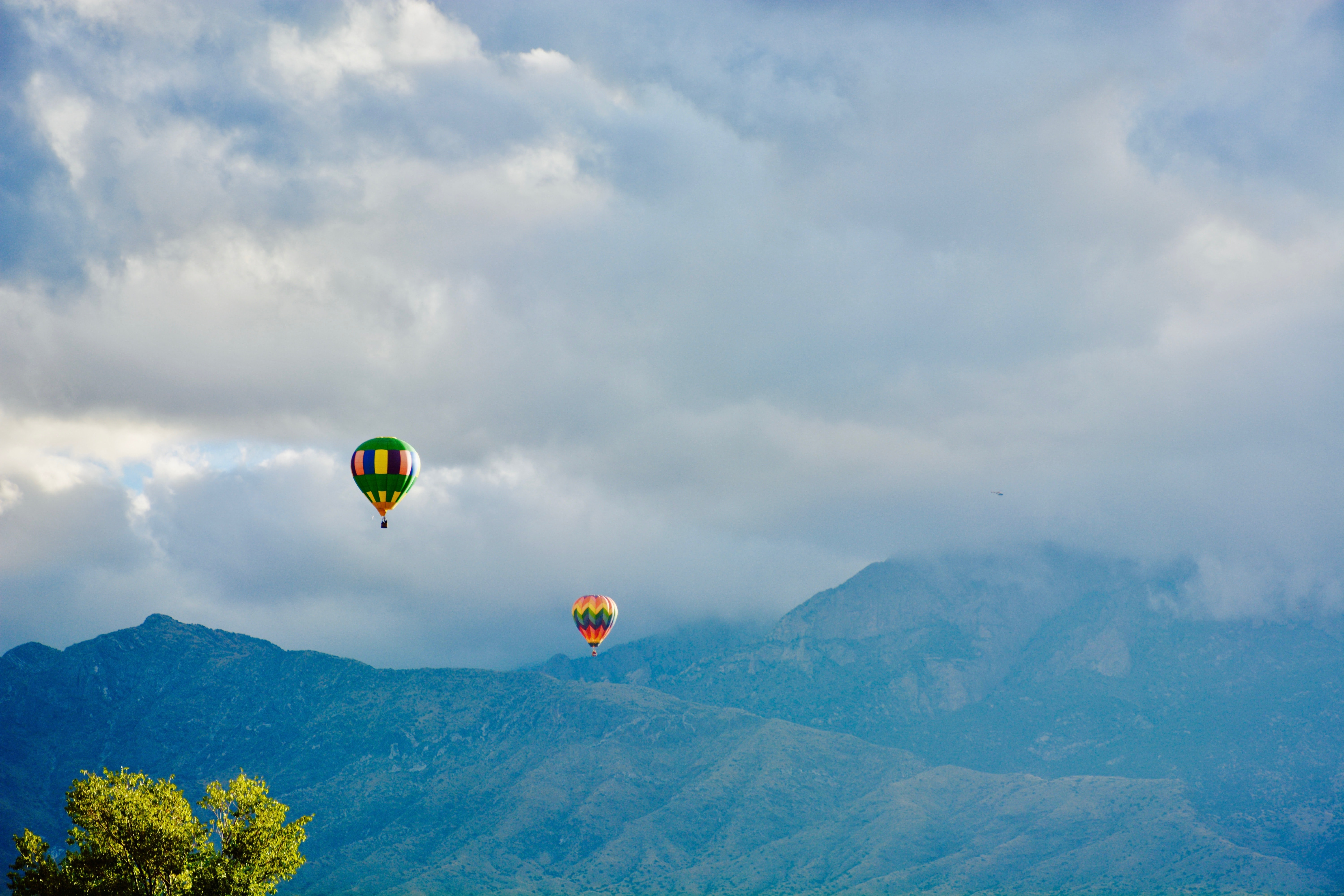 two hot air balloons near mountain