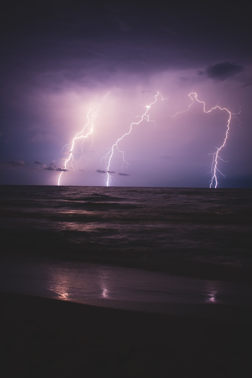 seashore and ocean with lightning during night time