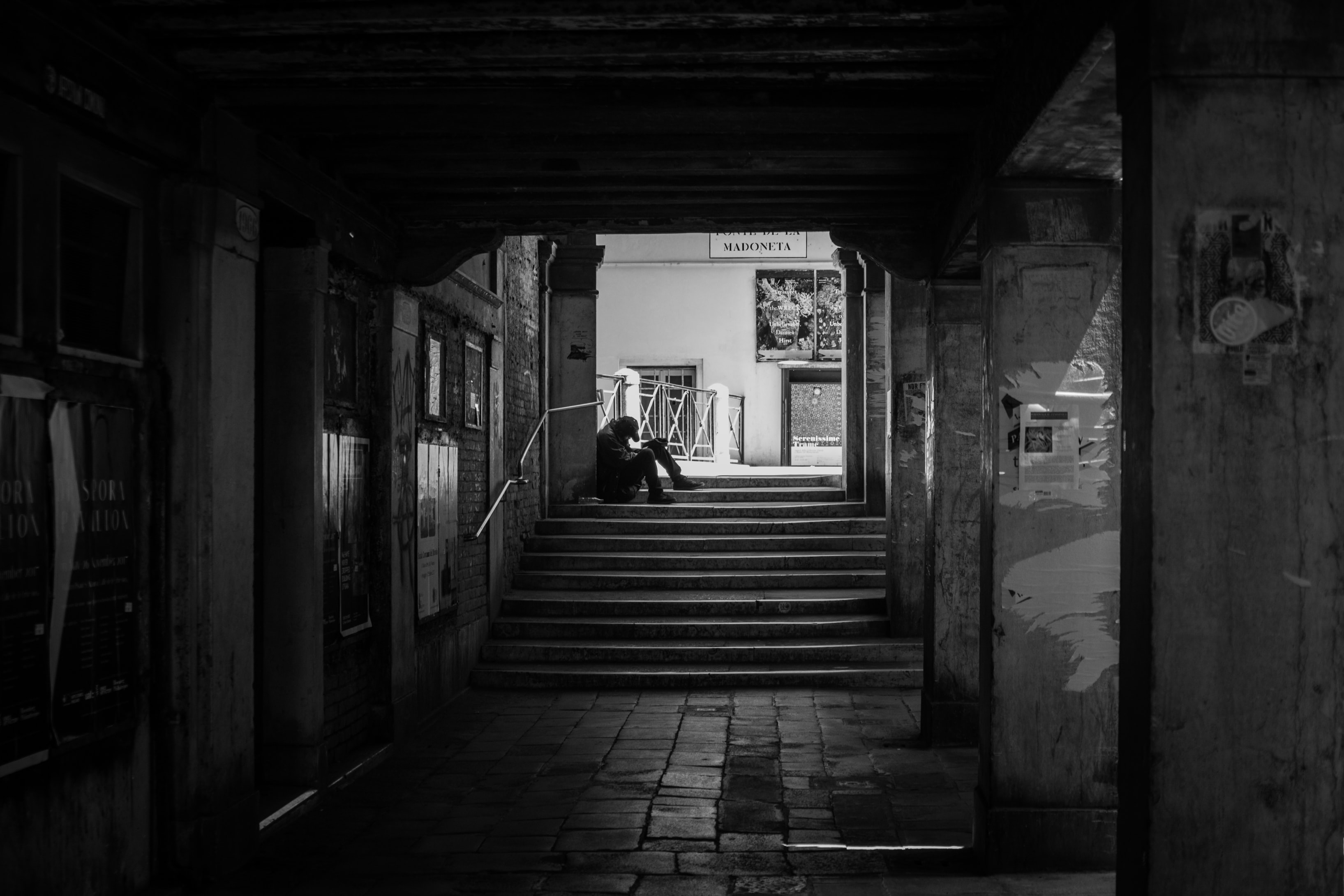 person sitting on gray stairs