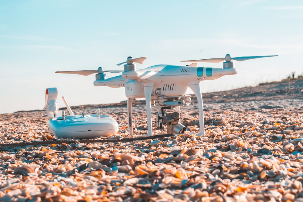 white DJI quadcopter and radio controller on rocky land