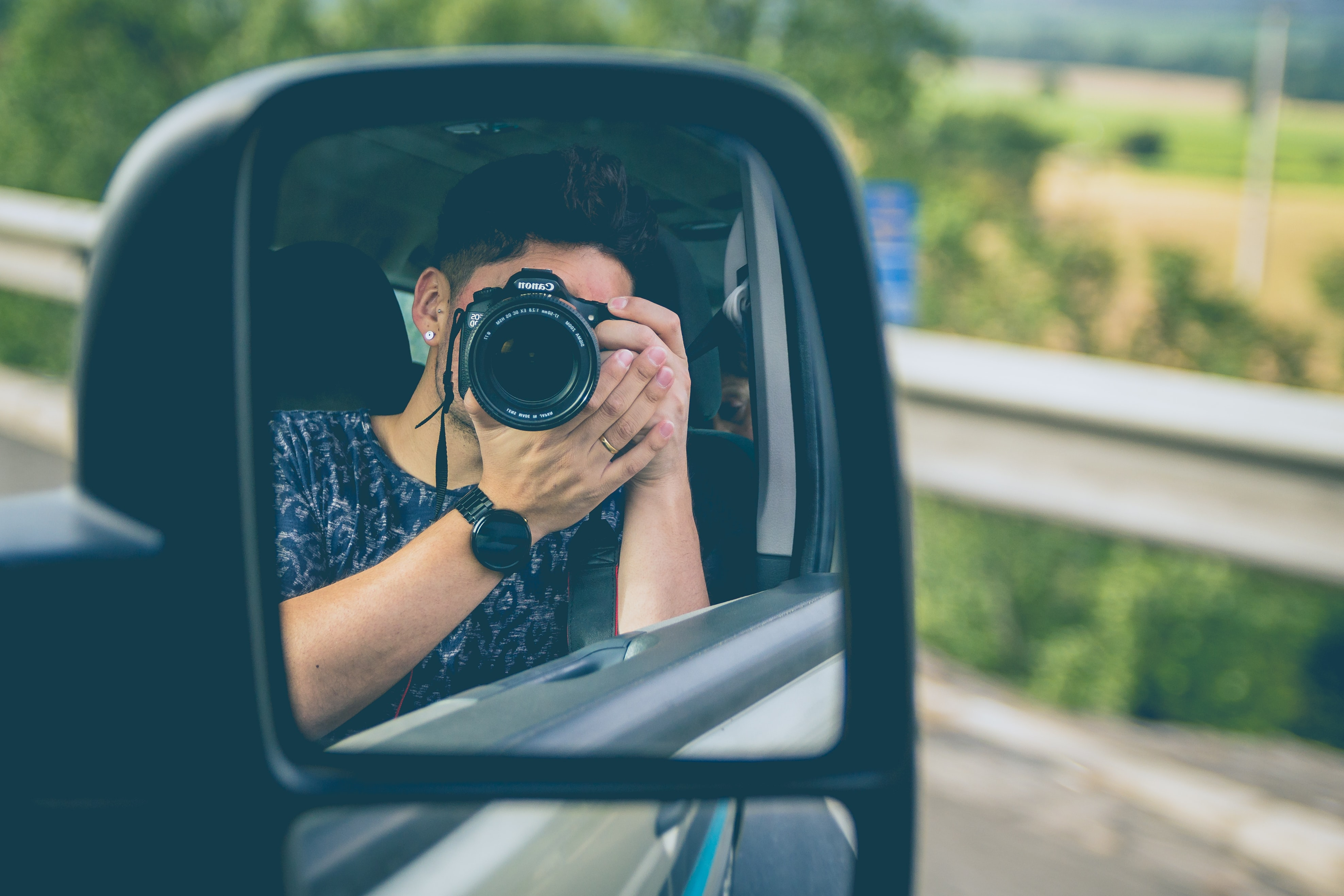 man taking picture on wing mirror