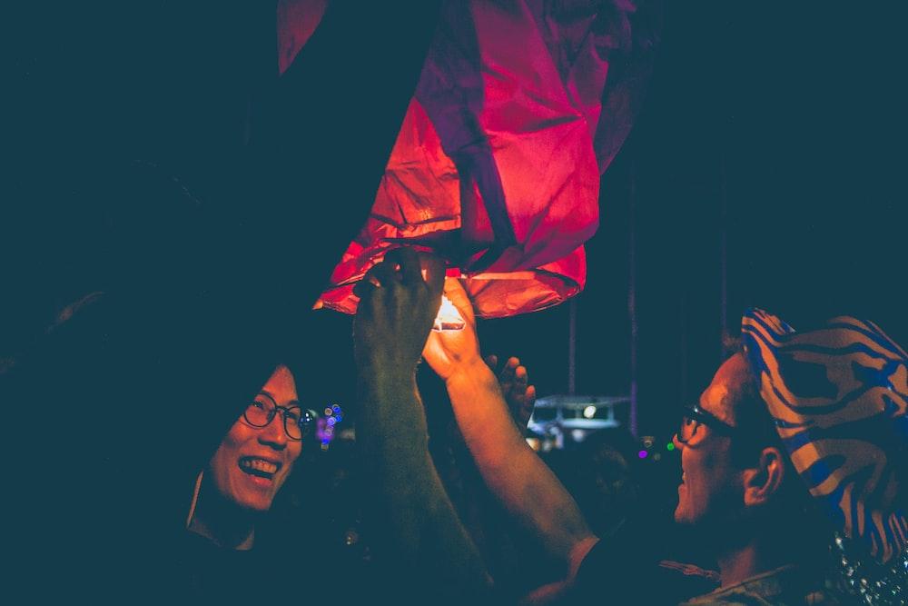 man lighting sky lantern during nighttime