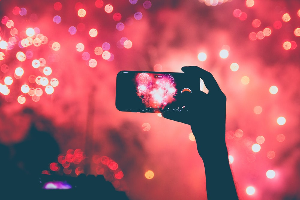 person taking a photo of fireworks using smartphoen