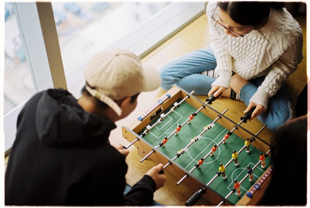 man and woman playing foosball table