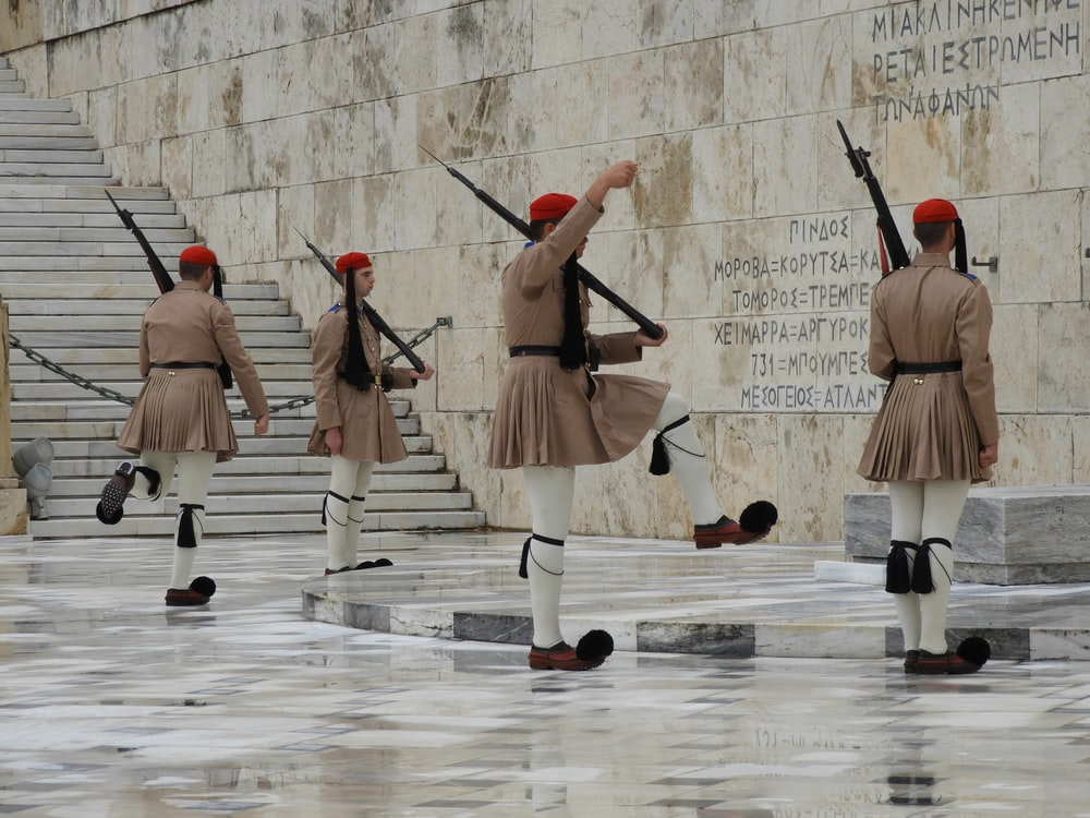 soldier wearing skirt standing infront of wall