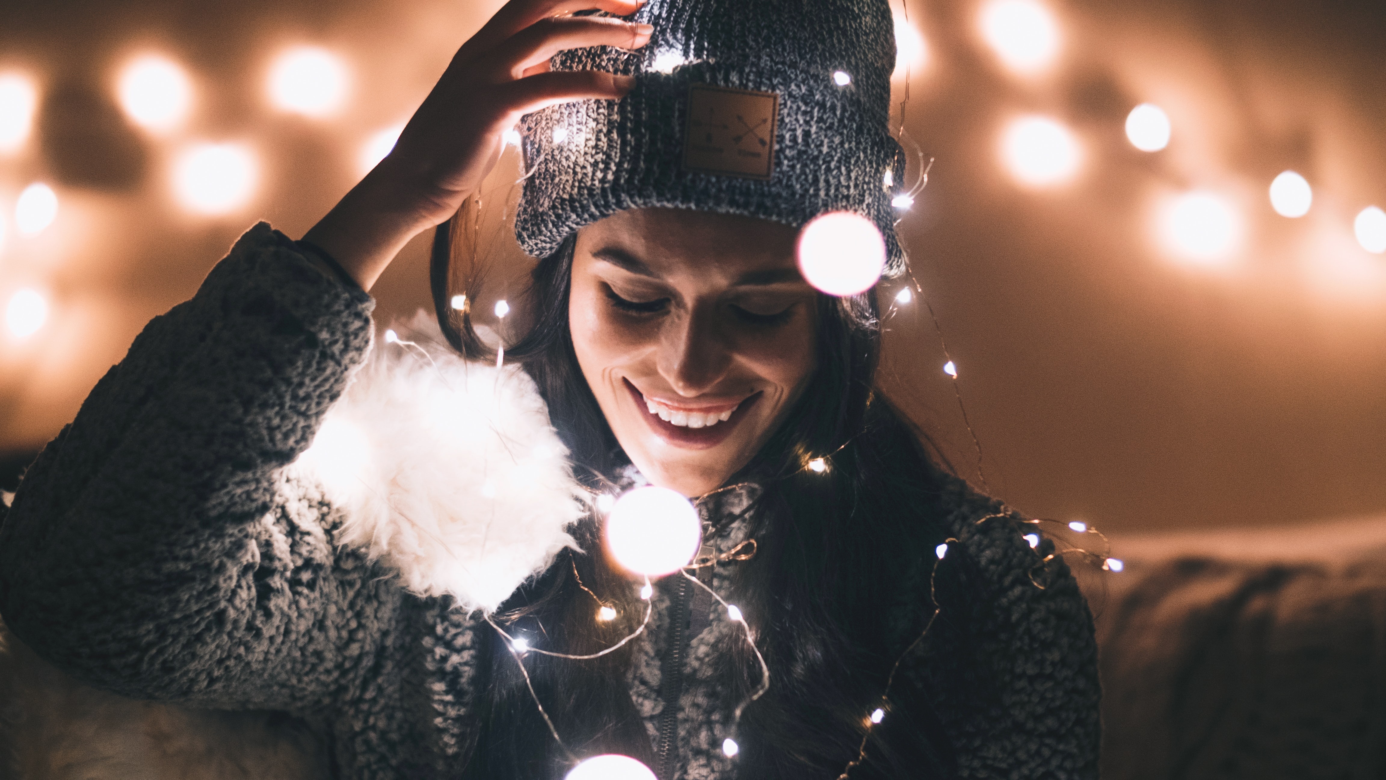 woman in black knit cap holding string lights