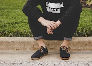 person sitting on sidewalk