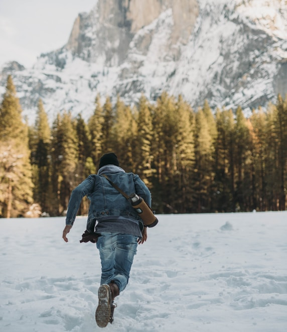 man running on snow near snowy mountain during daytime