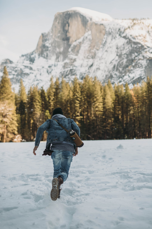 man running on snow near snowy mountain during daytime