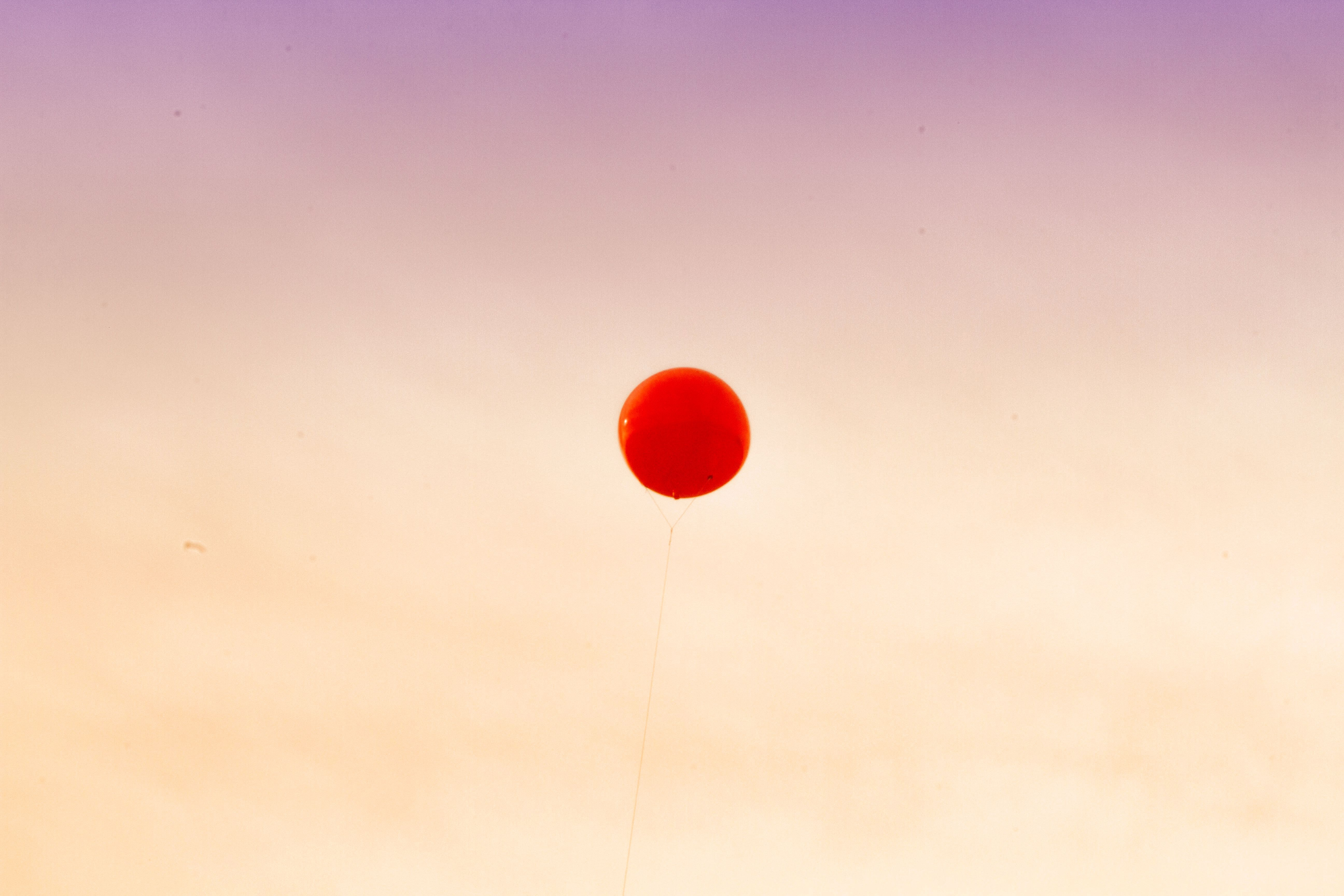 red balloon floating away the sky
