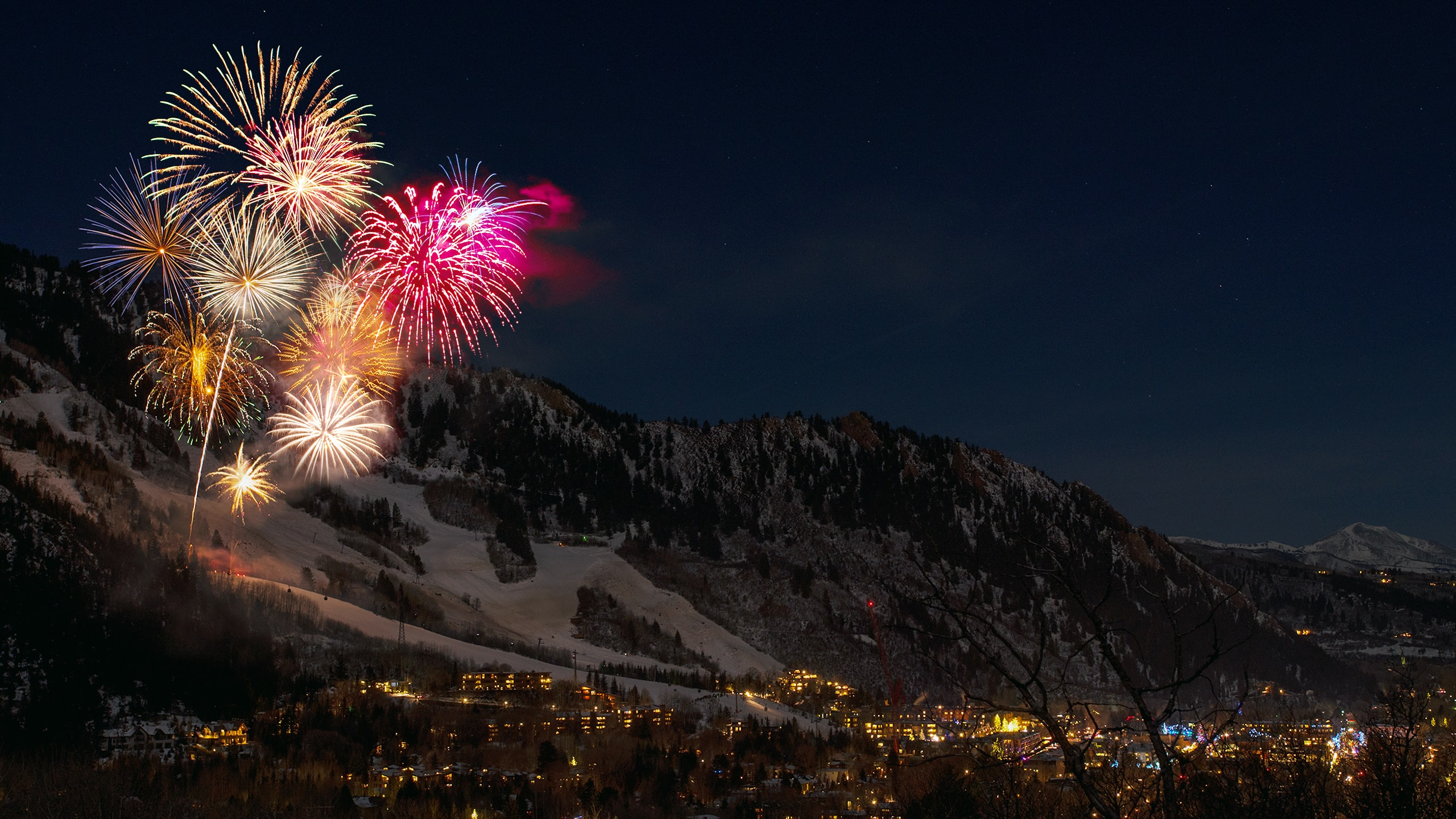 fireworks display from snow capped mountain during nighttime